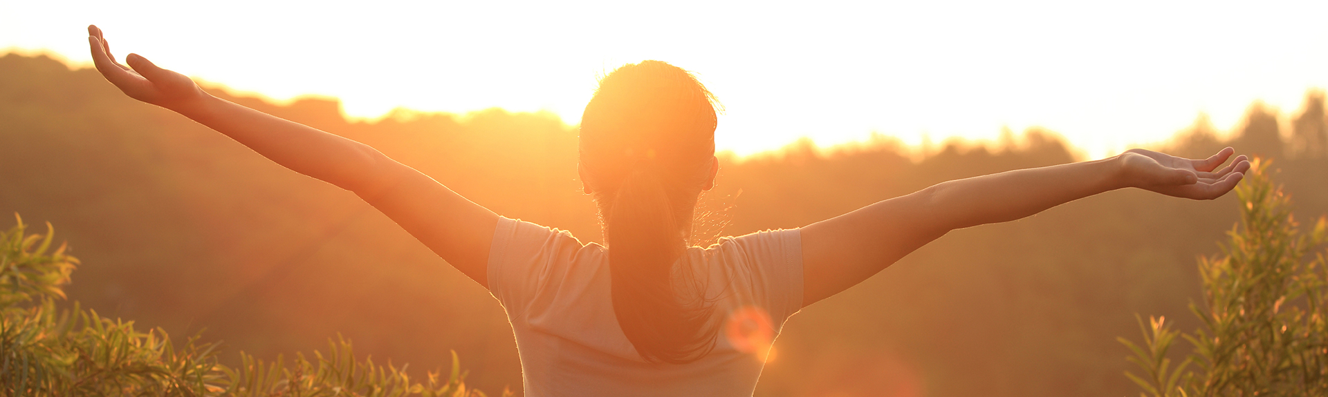 sun flare woman silhouette arms spread in nature